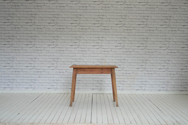 A vintage pine kitchen table on tapering legs