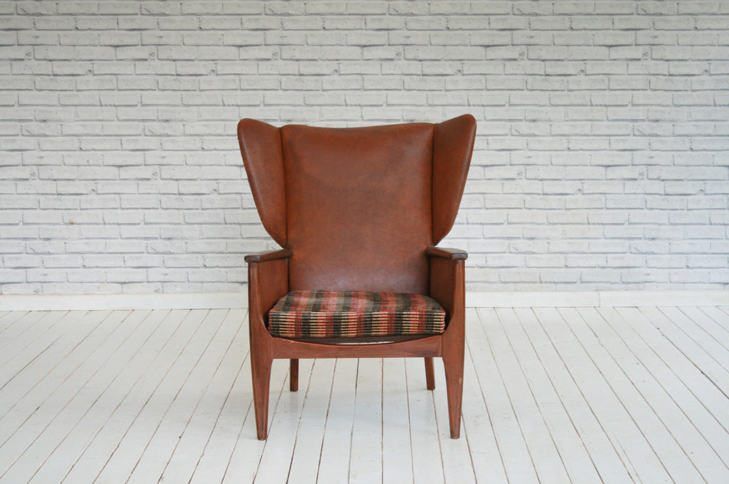 A vintage 1950/60s faux leather wing back armchair