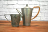 An antique hammered finish pewter coffee pot and milk jug