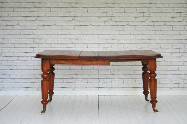 A Victorian mahogany extending dining table on brass castors