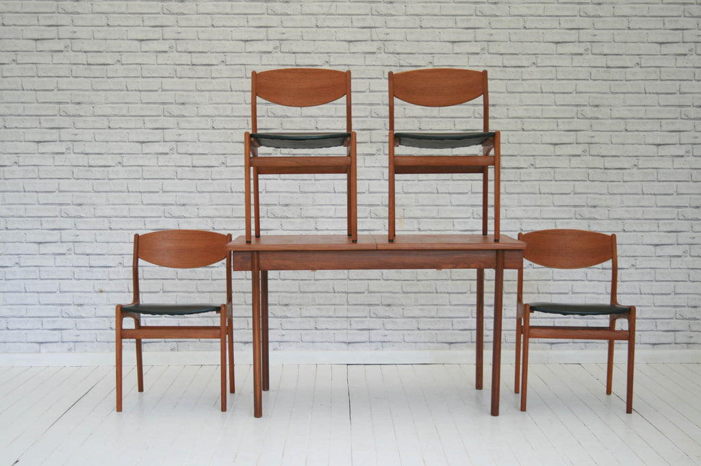 A 1970s G-Plan style teak extending dining table and four chairs