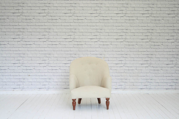 A Victorian button back open armchair on turned mahogany front feet