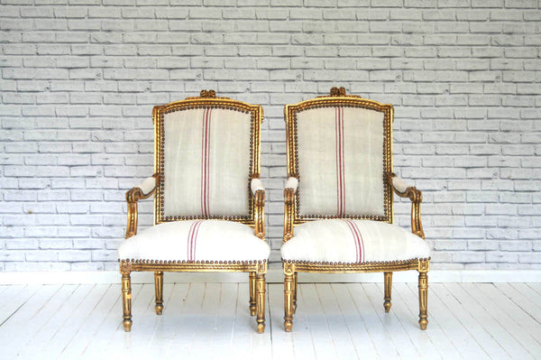 A stunning pair of antique French gilded armchairs