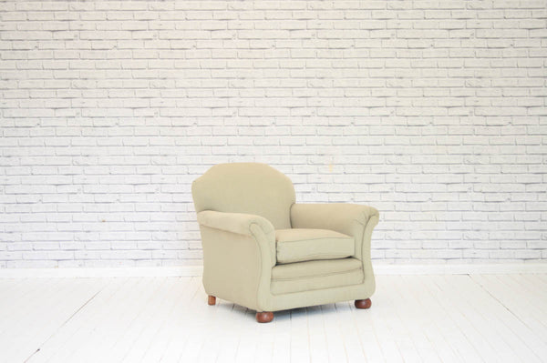 A deep seated Victorian armchair on bun feet