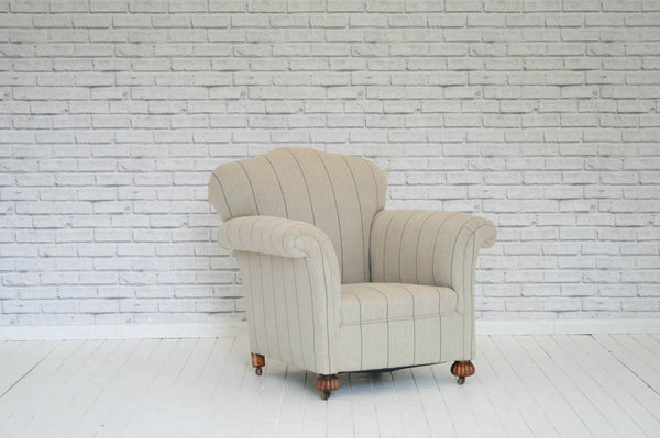 A deep seated Victorian armchair upholstered in pinstripe linen