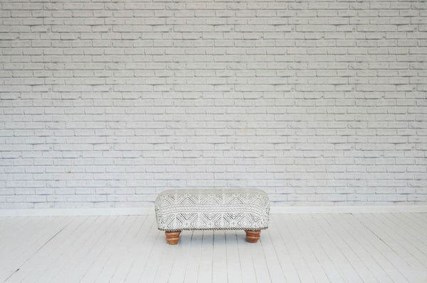 An ottoman upholstered in vintage Malian mudcloth with antique oversize brass studding