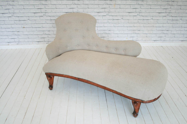 A Victorian chaise lounge on walnut sabre legs upholstered in heavy weave 100% linen