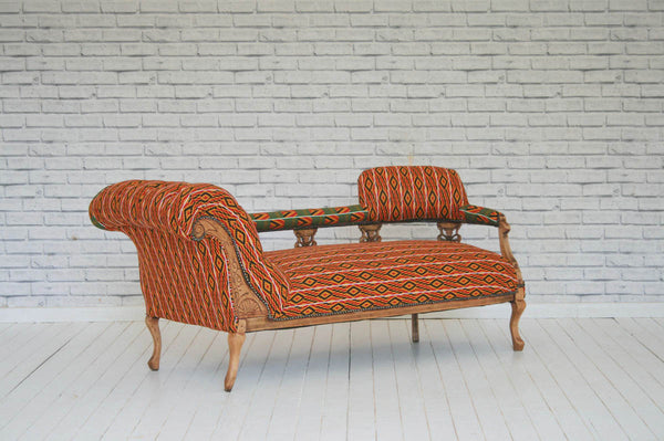 A Victorian gallery back chaise lounge upholstered in Rwandan Kitenge wax cloth