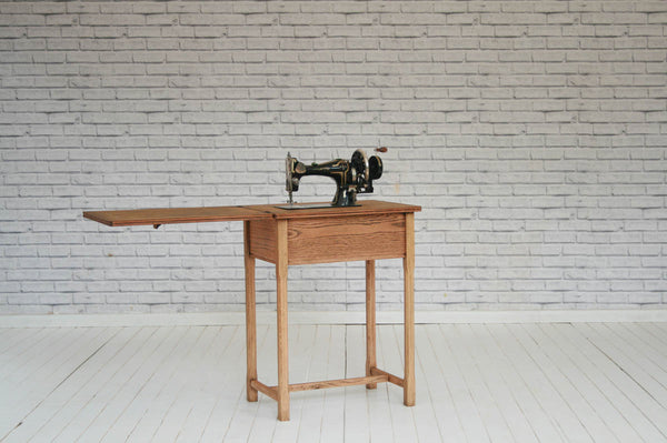 A 1930/40's Whiteley sewing machine in an oak table/Side table