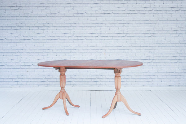 A mahogany twin pedestal D-end dining table