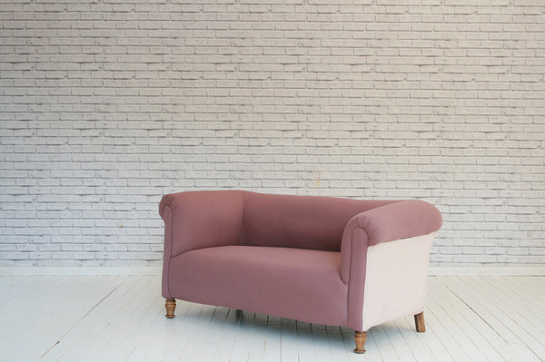 A Victorian two seater Chesterfield sofa in dusty pink cotton & ticking side panels