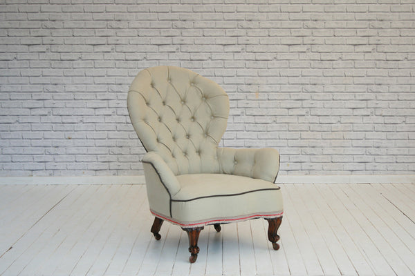 A Victorian button back armchair upholstered in soft grey cotton with Turkish braid border detail
