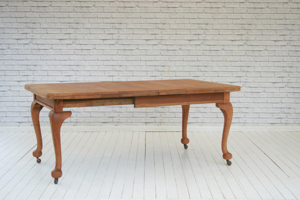 An Edwardian English Oak wind out dining table with two extra leaves