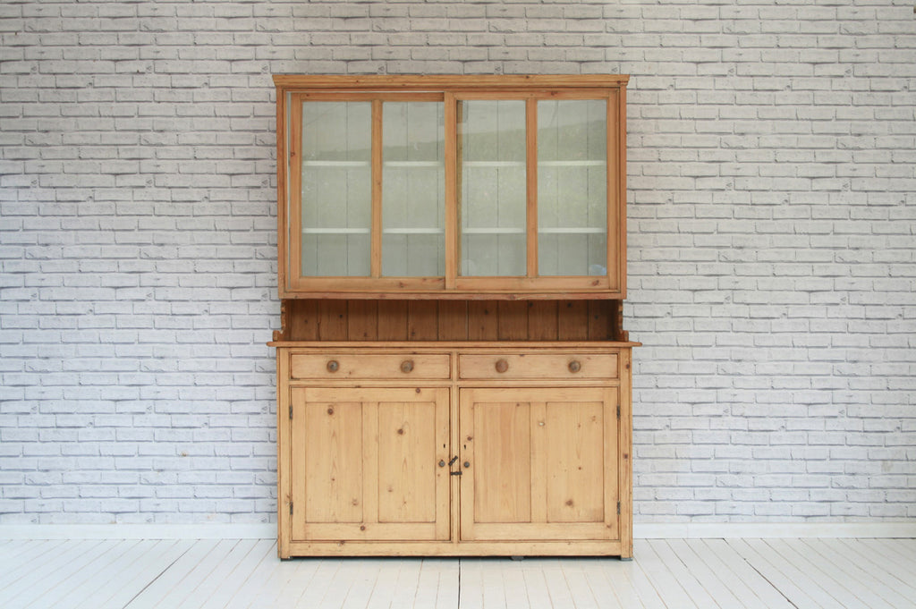 A 19th Century stripped pine kitchen dresser with glazed top over two drawer two door base