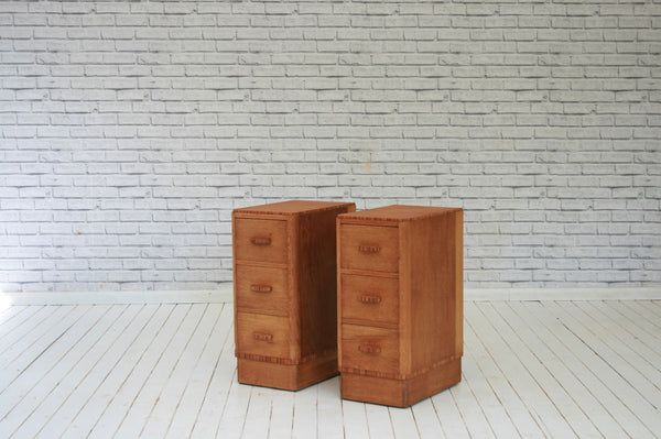 A pair of 1930's oak three drawer bedside tables