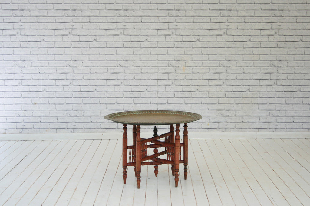 An Eastern brass top Binares occasional table with folding base