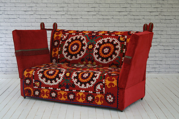 An Edwardian Knoll sofa upholstered in hand embroidered silk on cotton vintage Suzani & velvet