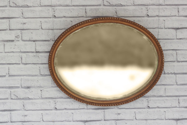 A vintage gilt framed oval mirror with bevelled edge.