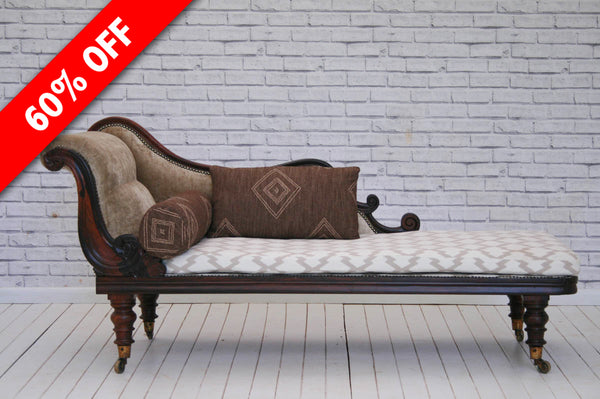 An ornate Victorian mahogany chaise lounge on large brass castors