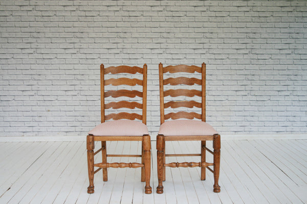 A pair of oak ladder back dining chairs