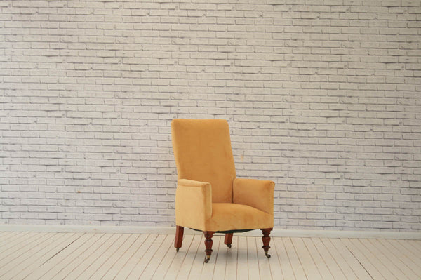 A high-backed Edwardian armchair on turned legs with brass castors