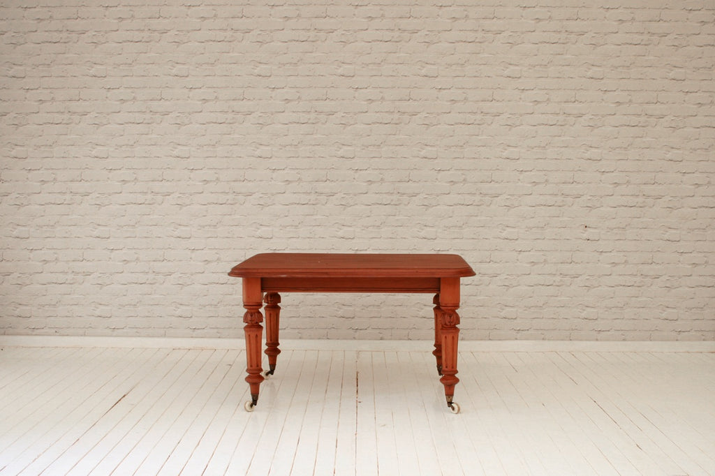 A Victorian mahogany round cornered dining table with carved and fluted legs to castors