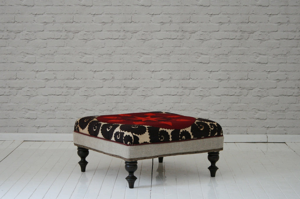 An antique Suzani covered ottoman/coffee table