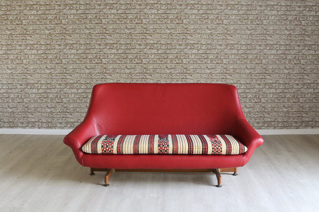 A 1960s vintage two seater sofa in faux red leather and West African Fulani blanket