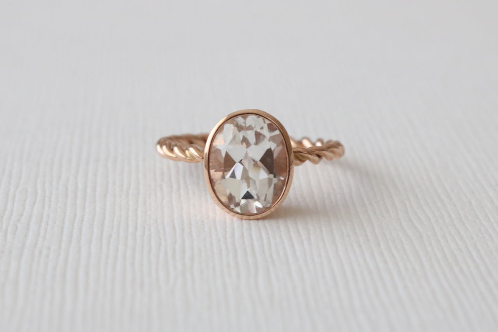 Oval White Topaz Bezel Twist Ring in 14K Rose Gold