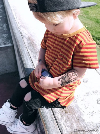 Little boy wearing temporary tattoo with legendary Volskwagen T1 hippie bus.