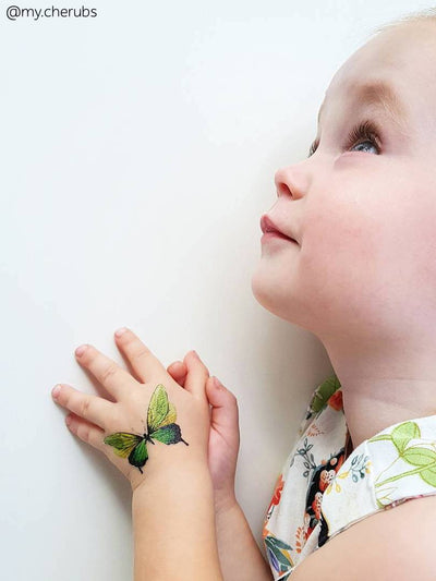 Adorable girl with hand drawn green butterfly temporary tattoo from big kids tattoos set Butterflies from Ducky street.
