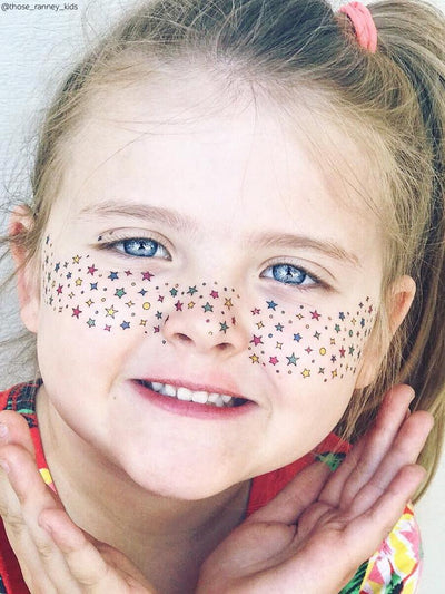 Girl with temporary freckles temporary tattoos. Rainbow stars freckles for party.