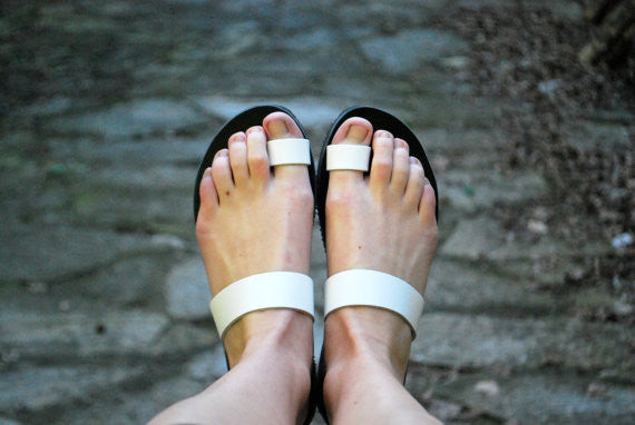 White straps on black leather toe rings side view