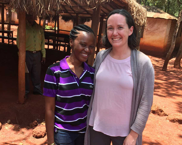 Erin and a Tanzanian woman smiling with an orange dirt background