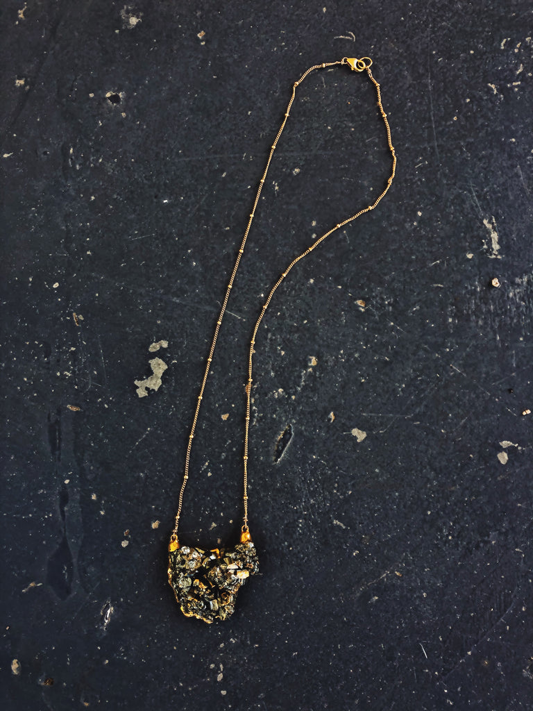 Raw pyrite grey stone necklace.  Organic shape encased in gold with dainty ball chain necklace. 20 inch chain.
