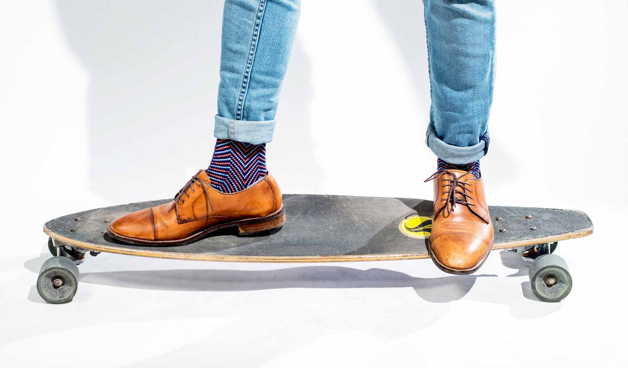 Light blue jeans with rolled cuffs, dark zig zag socks and brown shoes on a longboard.