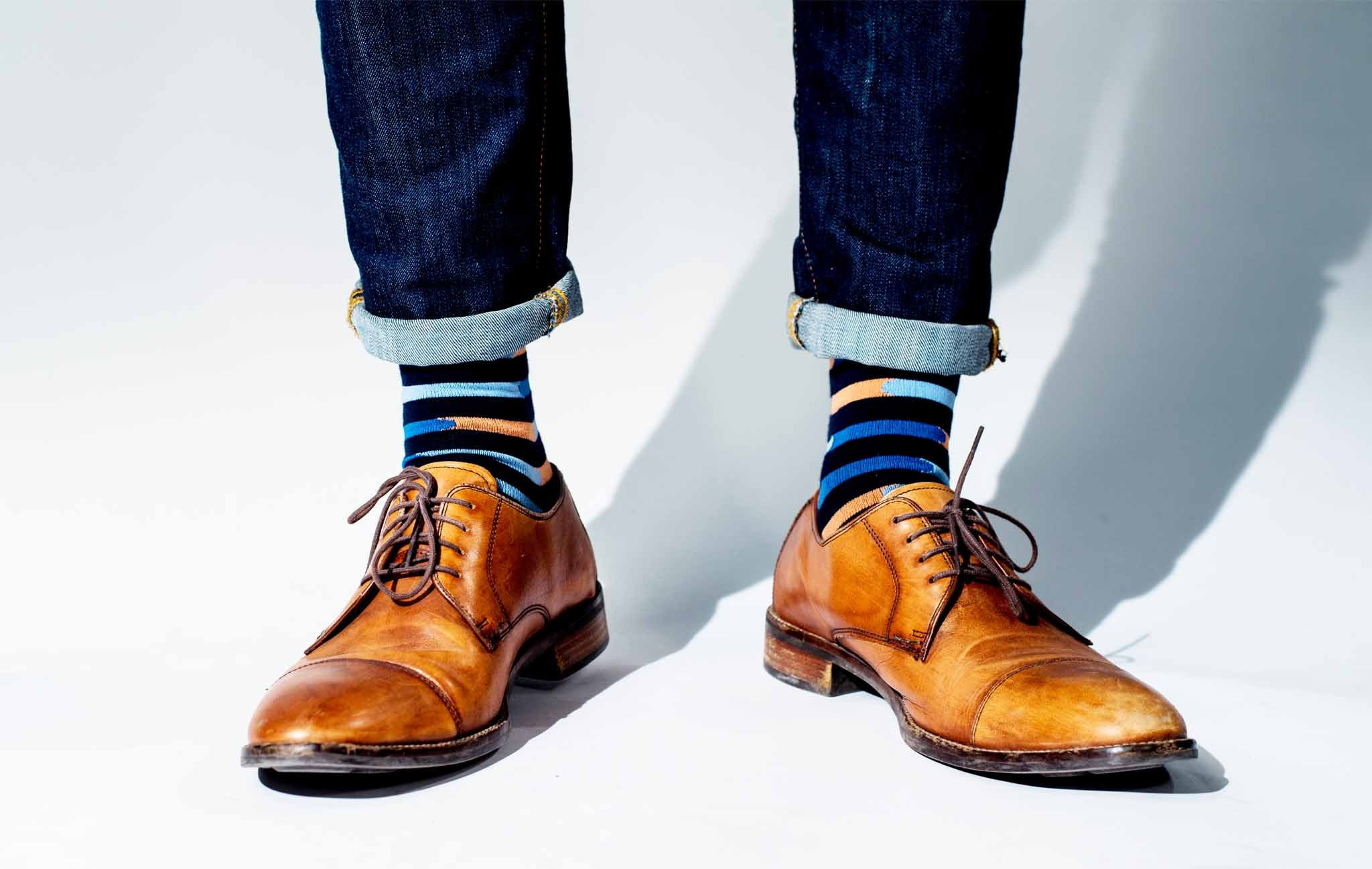 Striped black, light blue, dark blue and peach socks with brown shoes and jeans