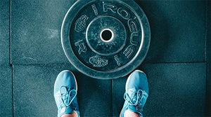 Looking-down-at-barbell-weight-with-sneakers-behind