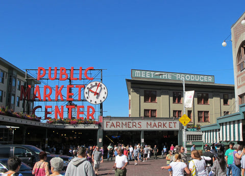 busy city farmers market with large red neon sign and clock