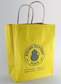 yellow paper gift bag with polish pottery place logo