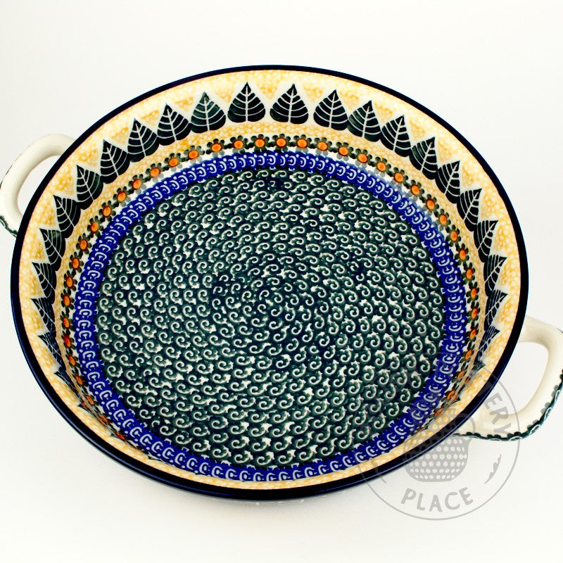 Large round polish pottery baker dish with handles and a big green leaf of with blue and yellow trim pattern