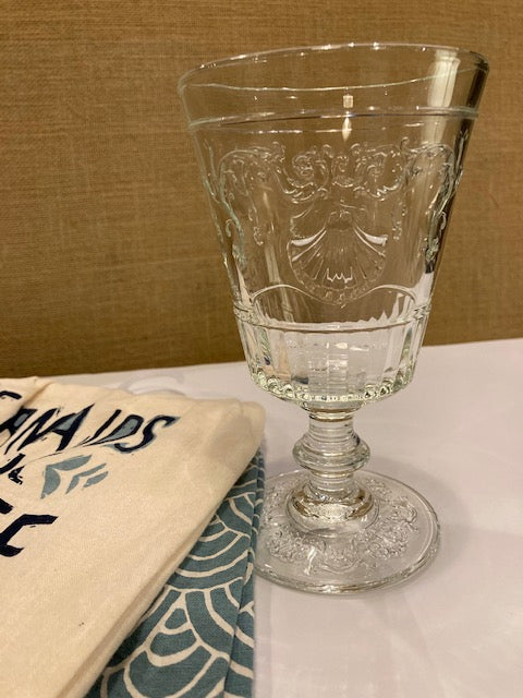 French drinking glass next to dishtowels