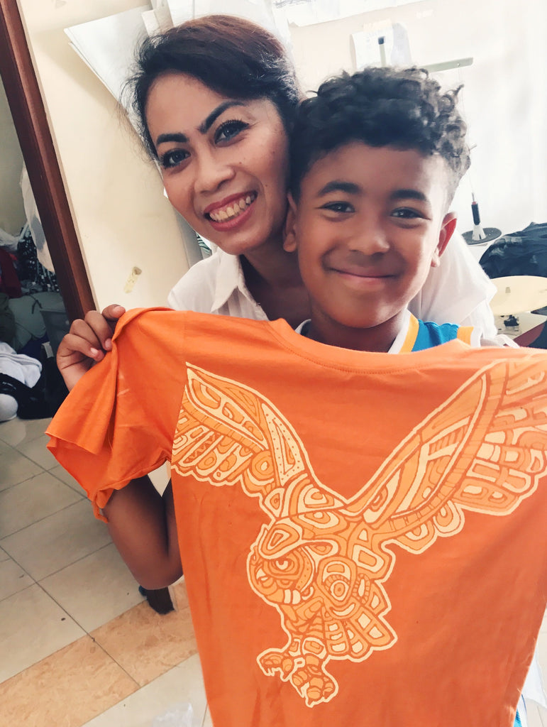 "Production manager Arti, with Andreas PEACE FITS owner's son, Sadiki. At Arti Bali, a family-owned factory.  Sadiki is holding one of our older kids tees with original Owl graphic from the ""EarthTRiBE"" collection"
