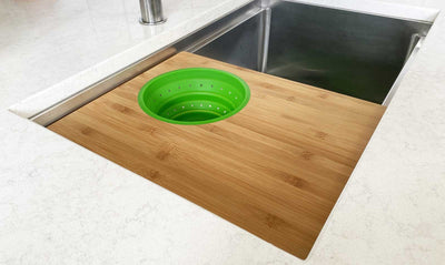 Seamless drain workstation sink with cutting board and green silicone colander