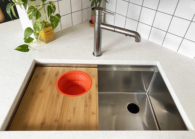 Seamless drain workstation sink with cutting board and silicone colander