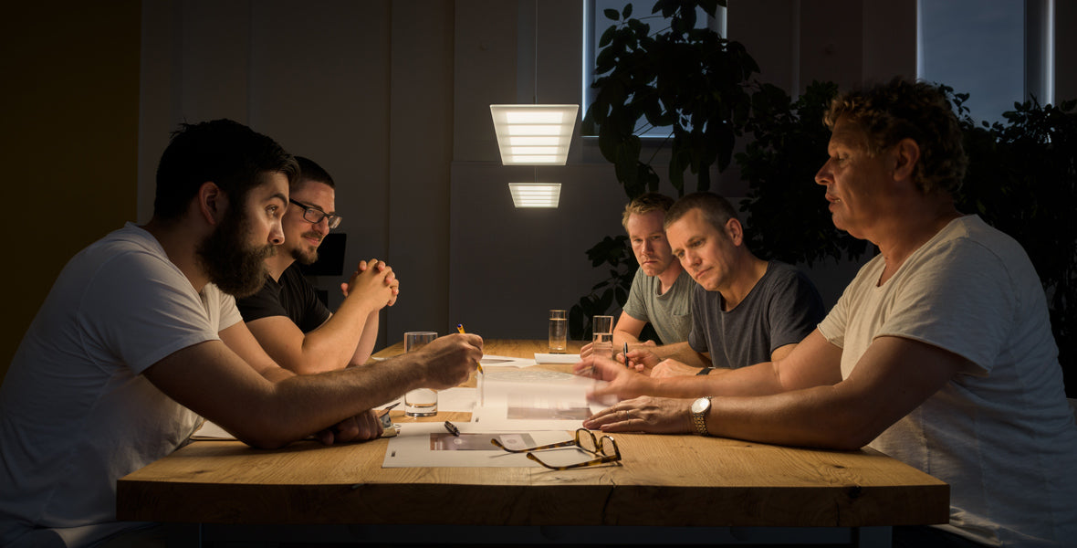 Emdedesign development team at a table with OLED-light