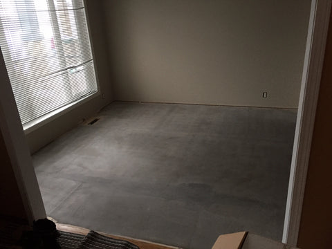 Multipurpose room with subfloor installed, covered in a leveling compound, and free of dirt or scraps