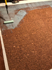 Contact cement being rolled onto the back of glue down cork flooring tiles.