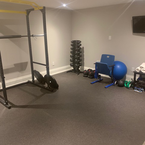 Rubber and cork flooring (boulder pattern) installed in a home gym with weight machines