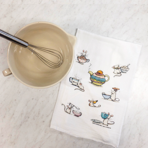 Paper Sharks Flour Sack Towel with a depiction of 7 white mice enjoying tea and biscuits in rows with a teapot in the center. The towel is next to a cream spouted Mason Cash mixing bowl with a whisk sitting inside